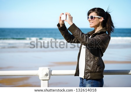 Joyful woman taking photo with cellphone on the beach on spring. Happy girl on vacation taking picture on sea background. - stock photo