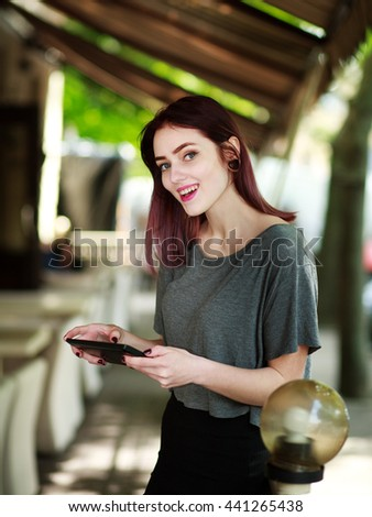 Joyful woman with tablet in summer cafe - stock photo