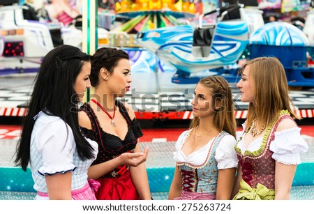 Joyful young and attractive women at German funfair Oktoberfest with traditional dirndl dresses and joyride in the background. Mixed nationalities, 2 girls rather typical German, one with Asian and - stock photo