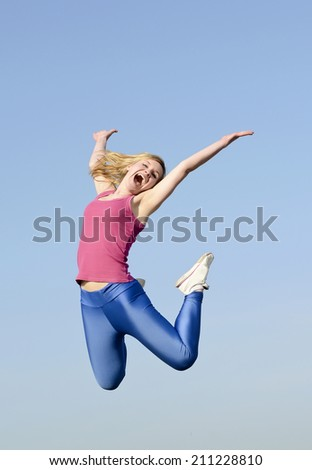 joyful young blond woman leaping - stock photo