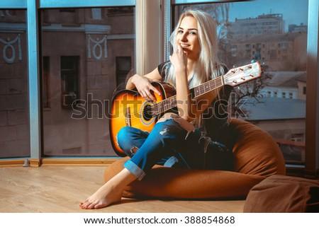 joyful young blonde girl plays guitar. Girl with guitar. Woman playing guitar. leisure with guitar. - stock photo