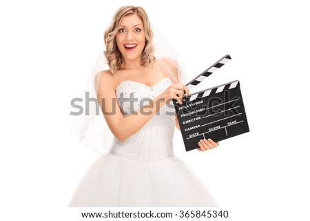 Joyful young bride in a white wedding dress holding a movie clapperboard isolated on white background - stock photo