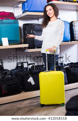 Joyful young brunette in white pullover selecting handy trunk in store and smiling