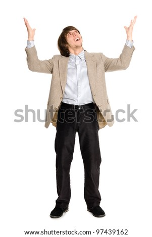 Joyful young business man with arms raised.