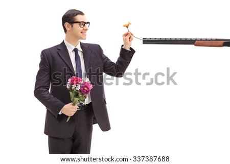 Joyful young businessman holding a bouquet of flowers and putting a flower in a rifle pointed at him isolated on white background