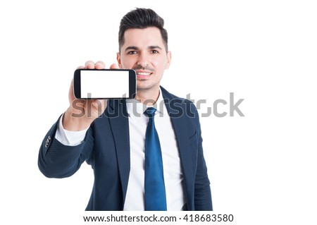 Joyful young businessman holding smartphone with blank screen and copyspace isolated on white background - stock photo