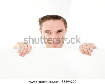 Joyful young cook holding a white paper smiling at the camera against white background - stock photo