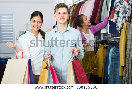 Joyful young couple holding shopping bags with many purchases at the clothing shop and smiling - stock photo