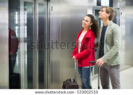 Joyful young couple with suitcases waiting for lift at subway station