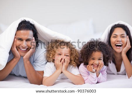 Joyful young family hiding under the blanket - stock photo