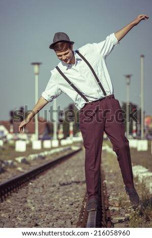 Joyful young fellow in white shirt with rolled up sleeves, hat and trousers with suspenders, trying to maintain his balance on a rail beside a railway platform. - stock photo