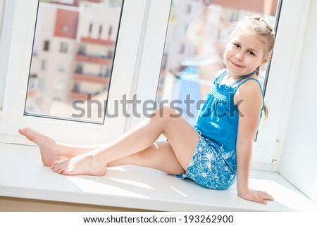 Joyful young girl in blue dress posing on window sill - stock photo