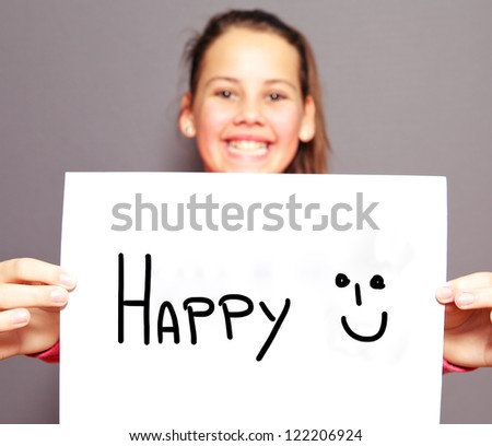 Joyful young girl with a HAPPY sign and smiley face handdrawn on a sheet of white paper with focus to the message - stock photo