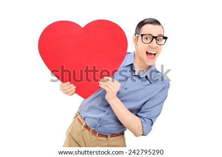 Joyful young man holding a big red heart isolated on white background - stock photo