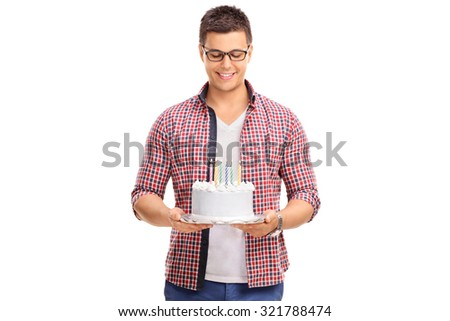 Joyful young man holding a birthday cake with a few candles on it isolated on white background