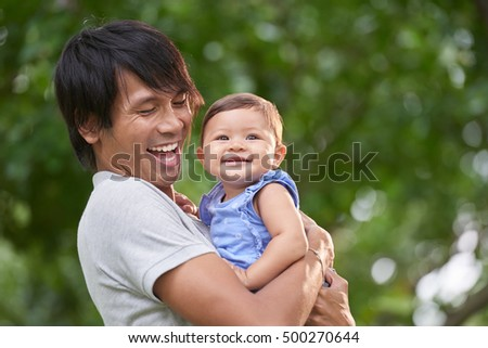 Joyful young man holding pretty little daughter