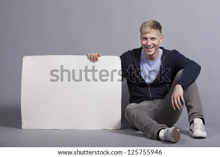 Joyful young man presenting white blank panel with space for text isolated on grey background.