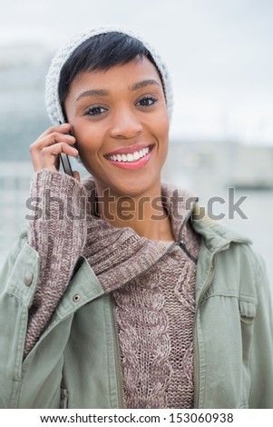 Joyful young model in winter clothes giving a phone call outside on a cloudy day - stock photo