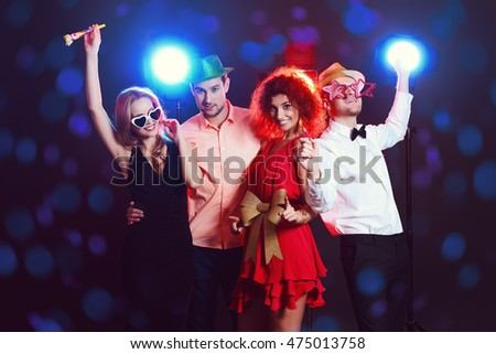Joyful young people dancing on a nightparty. Holidays, celebration.