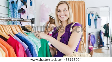 Joyful young woman choosing clothes with her friend in a shop