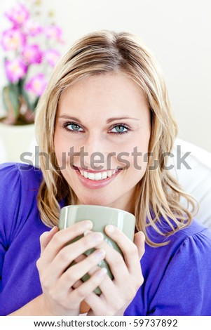 Joyful young woman holding a cup of coffee on a sofa at home