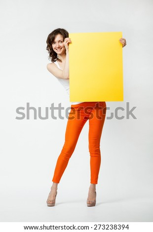 Joyful young woman in orange pants holding blank yellow placard, full length portrait on neutral background - stock photo