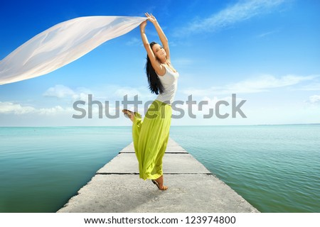 Joyful young woman jumping with white tissue against seascape - stock photo