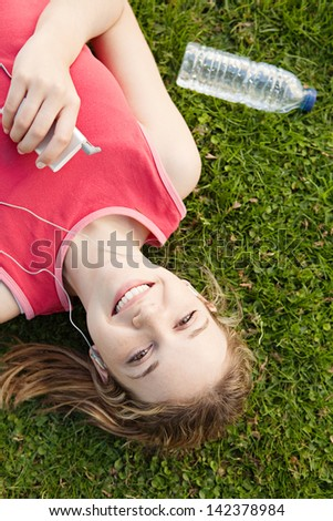 Joyful young woman laying down on a park green grass, taking a break from exercising while listening to music with her mp4 player and earphones. - stock photo
