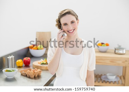 Joyful young woman phoning with her smartphone standing in kitchen smiling at camera - stock photo