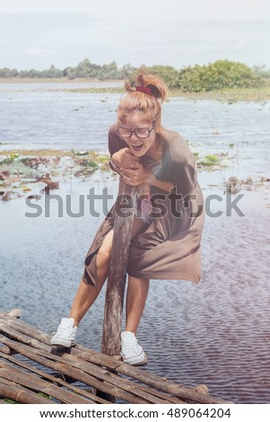 joyful young woman relaxing on the wooden balcony at the lake