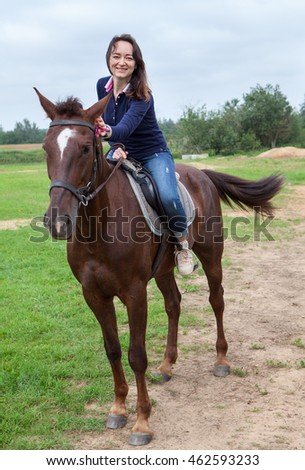 Joyful young woman touching her chestnut horse while riding on field