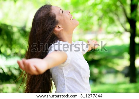 Joyful young woman with arms outstretched in park. Attractive mixed race Asian / Caucasian female is in casuals. She is looking up while smiling. - stock photo
