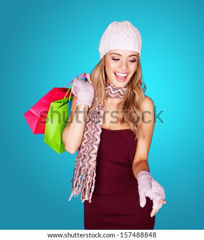 Joyful young woman with shopping bags wearing a trendy cap, scarf, and gloves laughing as she dangles the brightly coloured bags over her shoulder, over blue - stock photo