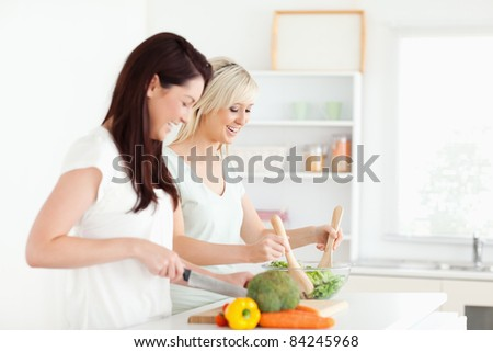 Joyful young Women preparing dinner in a kitchen
