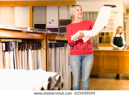 joyous aged woman customer looking for beautiful fabric in home textile shop