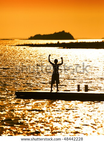 Joyous Boy Standing On Dock On Beautiful Afternoon - stock photo