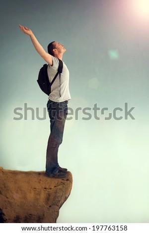 joyous man arms aloft giving praise on a rocky outcrop - stock photo