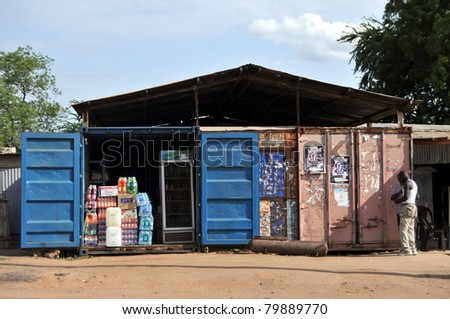 JUBA - JUNE 10: Unidentified men standing in front of containers turned into a shop in Juba, capital of South Sudan, on June 10, 2011. Containers are used in Juba for everything from shops to hotels. - stock photo