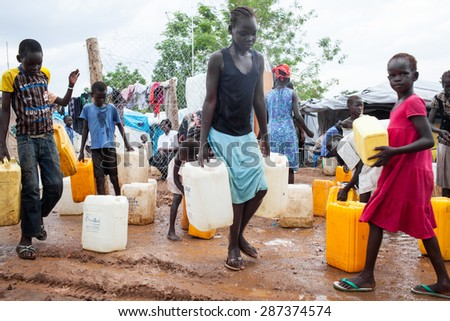 Juba, South Sudan - April 10, 2014: South Sudanese children get the daily ration of water - stock photo