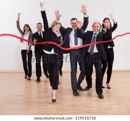 Jubilant business people celebrating raising their arms in the air and shouting as they cut the red ribbon to begin a new business venture - stock photo