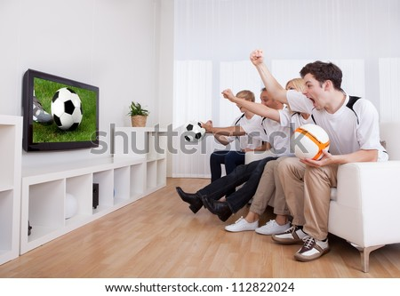 Jubilant family watching television as they cheer on their home side in a sporting competition - stock photo