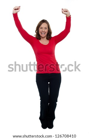 Jubilant lady celebrating her success, throwing up her hands in the air, full length. - stock photo