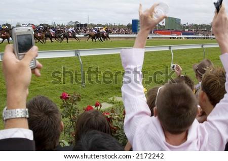 Jubilant spectators encourage their horses across the line - stock photo