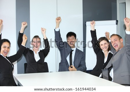 Jubilant successful business team of motivated multiethnic young people sitting celebrating and cheering at a table in the office with broad smiles