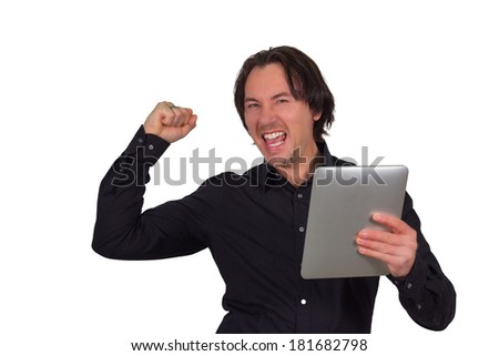 Jubilant young man holding a tablet computer in his hand celebrating good news by punching the air with his fist and yelling isolated on white