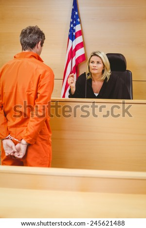 Judge and criminal speaking in front of the american flag in the court room - stock photo