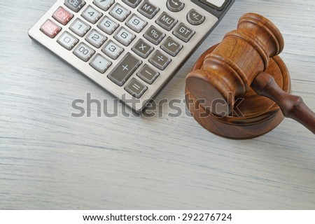 Judge gavel and calculator on white table, arbitration concept - stock photo
