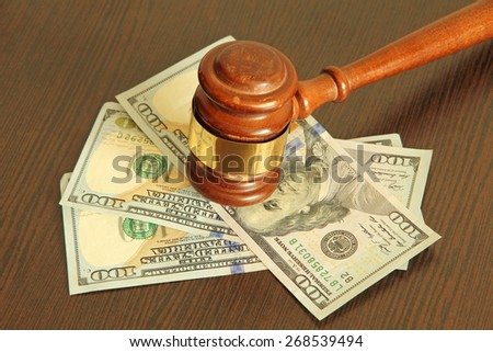 Judge gavel and dollar banknotes on wooden table taken closeup. - stock photo