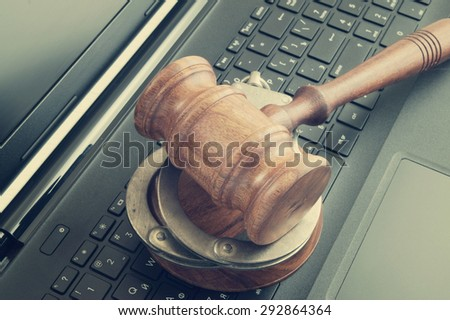 Judge gavel and handcuffs on laptop computer - stock photo