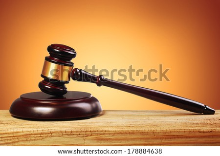 Judge gavel and soundboard over gold background - stock photo